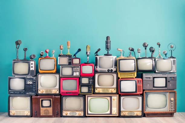 Retro-TV-Empfänger aus ca. 60er, 70er und 80er Jahren des XX Jahrhunderts, alte klassische Mikrofone für Pressekonferenz Front mint blau Wand Hintergrund. Rundfunk, Nachrichtenkonzept. Vintage-Stil gefiltertfoto – Foto