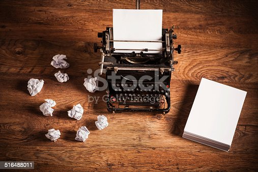 istock Retro typewriter on a wooden desk 516488011