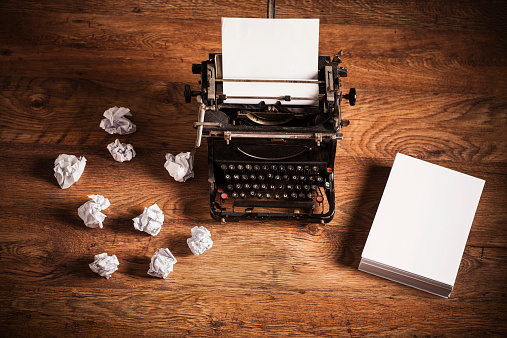 Retro typewriter on a wooden desk and a stack of paper beside it