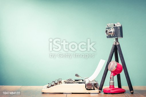 istock Retro typewriter, outdated film photo camera on tripod and old microphone on wooden table front mint green wall background. Blogging concept. Vintage style filtered photo 1047484122