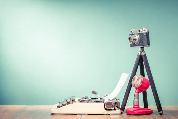 Retro-Schreibmaschine, veraltete Film-Foto-Kamera auf Stativ und alten Mikrofon auf Holztisch vorne mintgrün Wand Hintergrund. Blogging-Konzept. Vintage-Stil gefilterten Foto – Foto