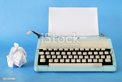 Manual Typewriter Circa 1970 with a blank sheet of paper and rejected work alongside