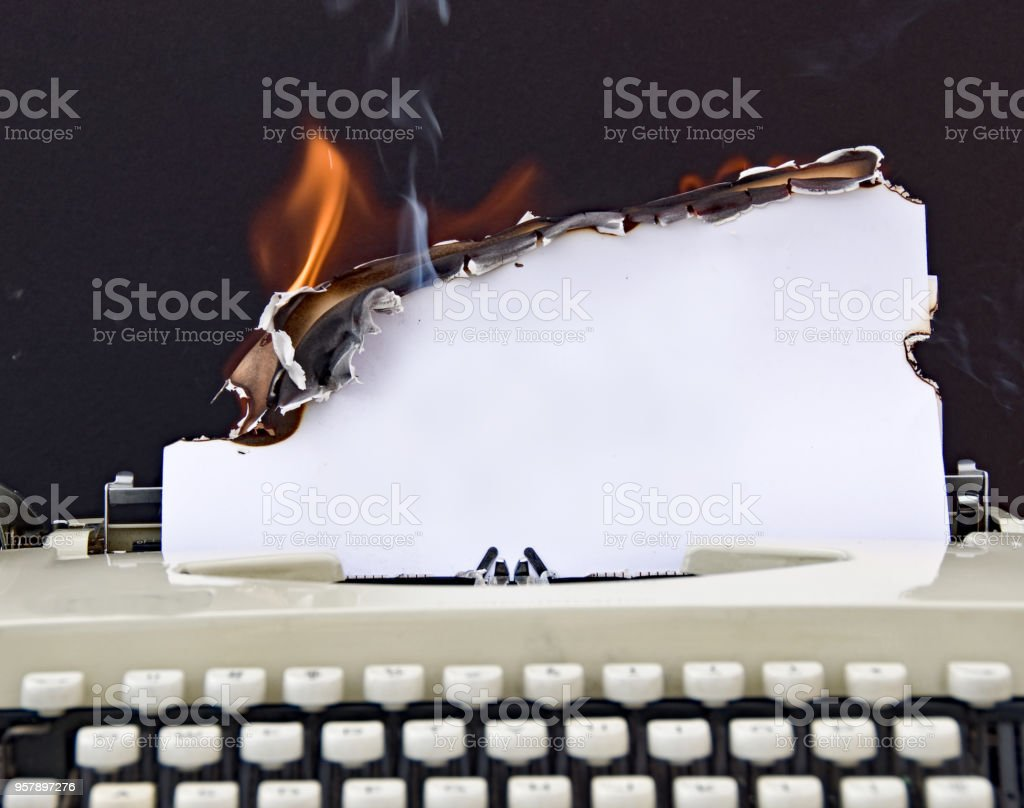 Retro typewriter with burning paper as copy space stock photo