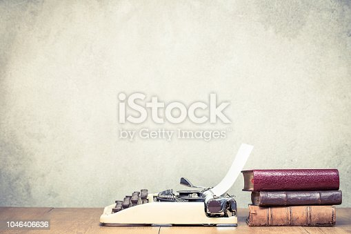 istock Retro typewriter with sheet of paper and old books on wooden table front concrete wall background. Vintage style filtered photo 1046406636