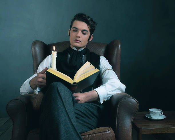 retro victorian dickens style man reading book by candlelight. - charles dickens weihnachtsgeschichte stock-fotos und bilder