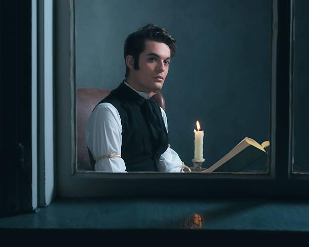 retro victorian man reading book by candlelight sitting by window. - charles dickens weihnachtsgeschichte stock-fotos und bilder
