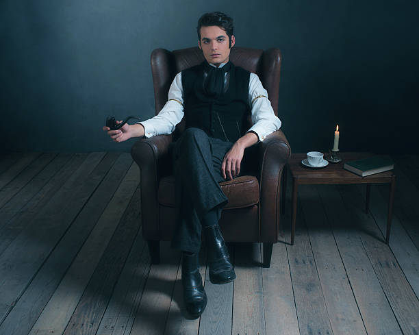 retro victorian man sitting in leather chair holding pipe. - charles dickens weihnachtsgeschichte stock-fotos und bilder