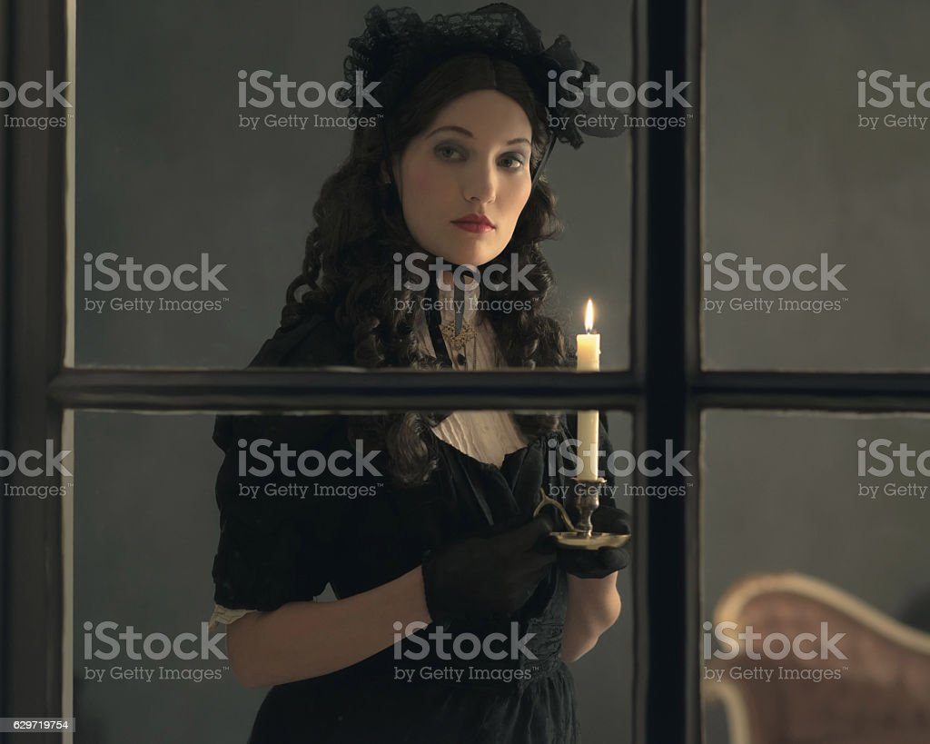 Retro victorian woman in black dress behind window holding candlestick. stock photo