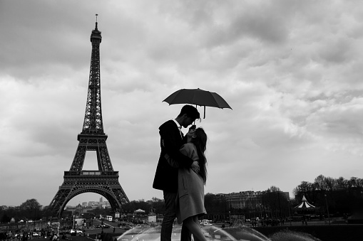 retro view of Paris, couple under umbrella near Eiffel tower, vintage