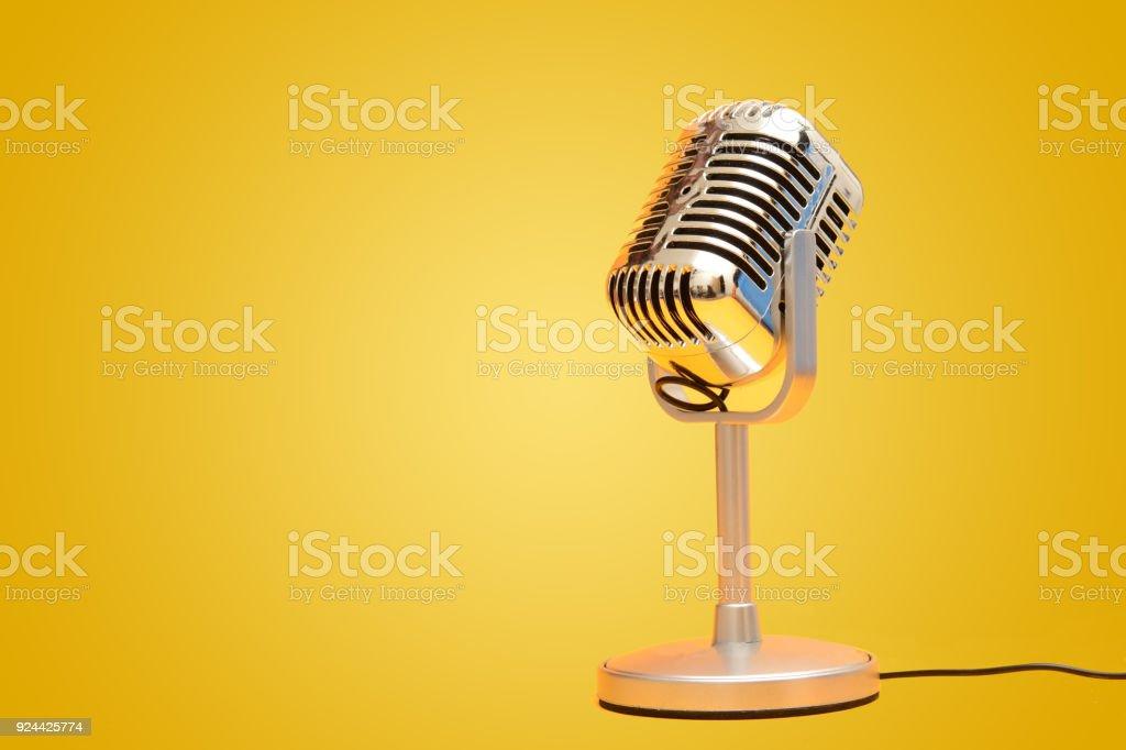Retro vintage microphone on yellow background studio stock photo