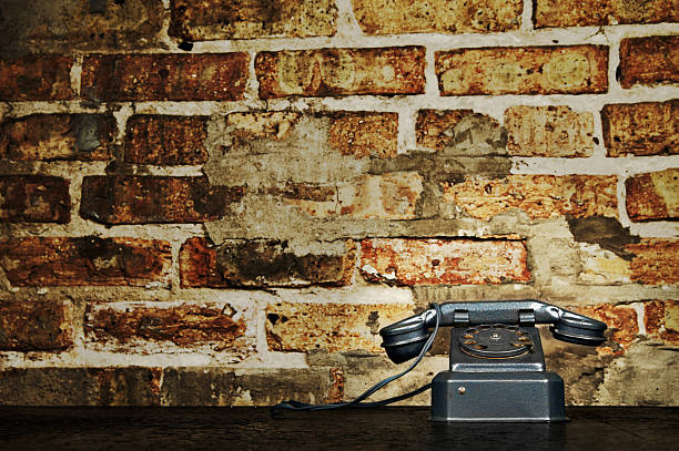 Retro Vintage  Phone Telephone on Old Desk with Brick Wall stock photo