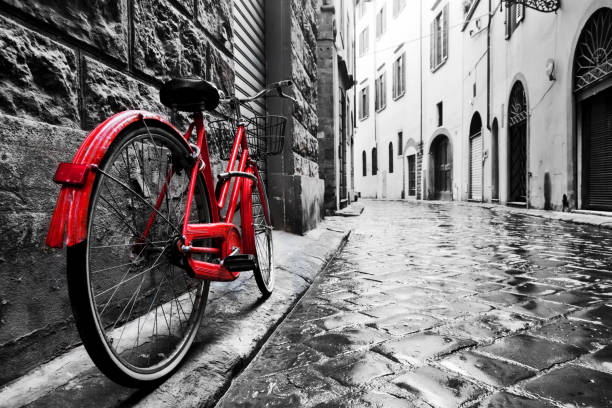 Retro vintage red bike on cobblestone street in the old town. Color in black and white stock photo