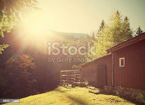 Retro vintage stylized mountain shelter against sun with flare effect.