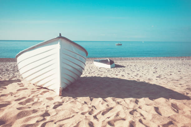 Retro vintage toned fishing boat on the beach in Calaria