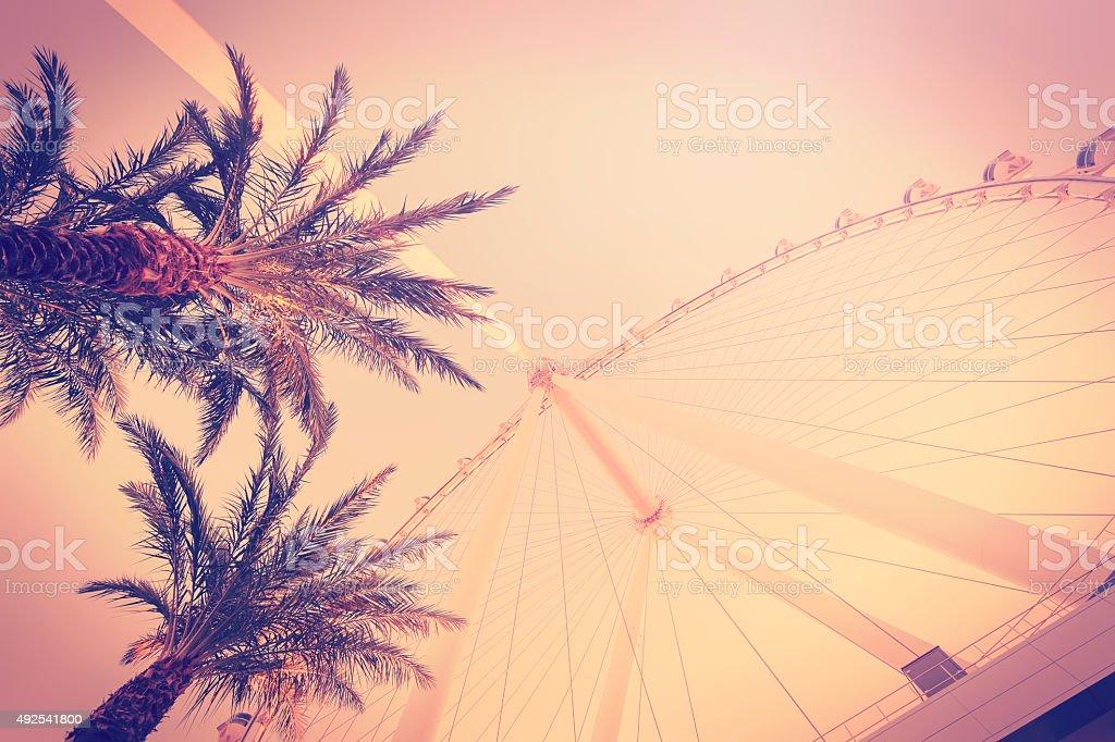 Retro vintage toned photo of palms and ferris wheel. stock photo