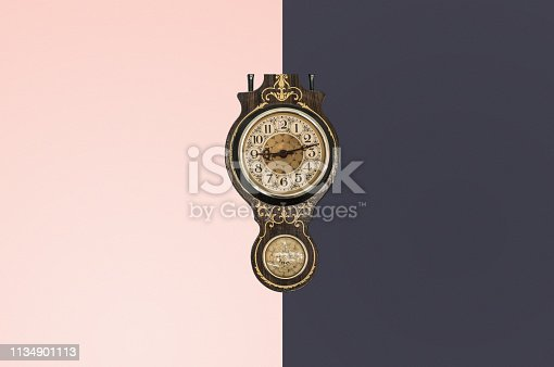 Retro wall clock hanging on a colored background