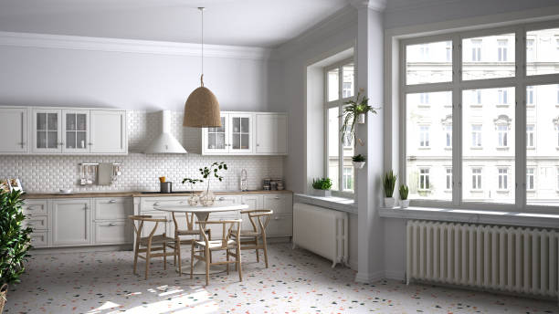Retro white vintage kitchen with terrazzo marble floor and panoramic windows, dining room, round table with wooden chairs, potted plants, radiators, pendant lamp, cozy interior design stock photo