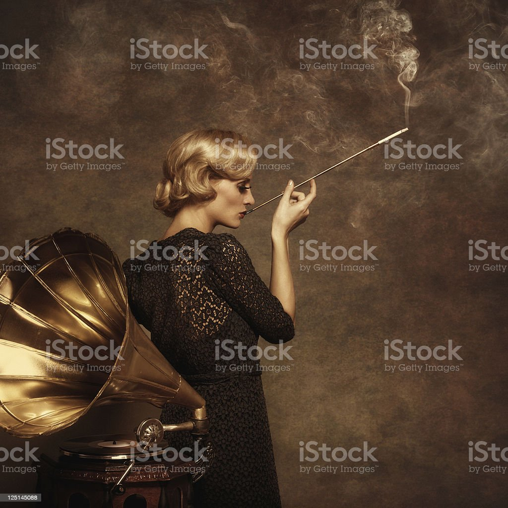 Retro woman listening to music and smoking cigarette royalty-free stock photo