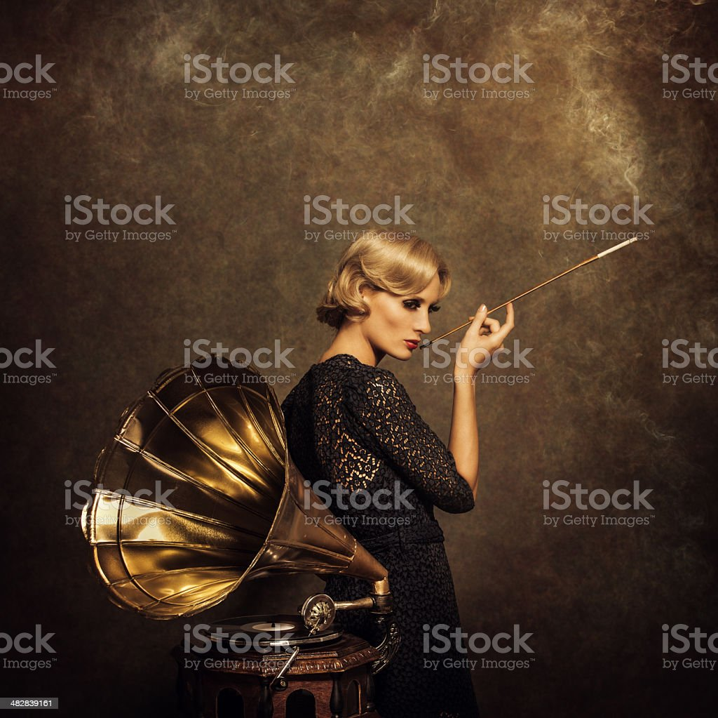 Retro woman listening to music and smoking cigarette stock photo
