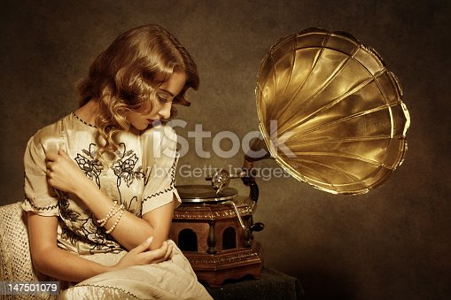 Retro woman sitting and listening to music on gramophone - added real film grain and brown tone for the mood.