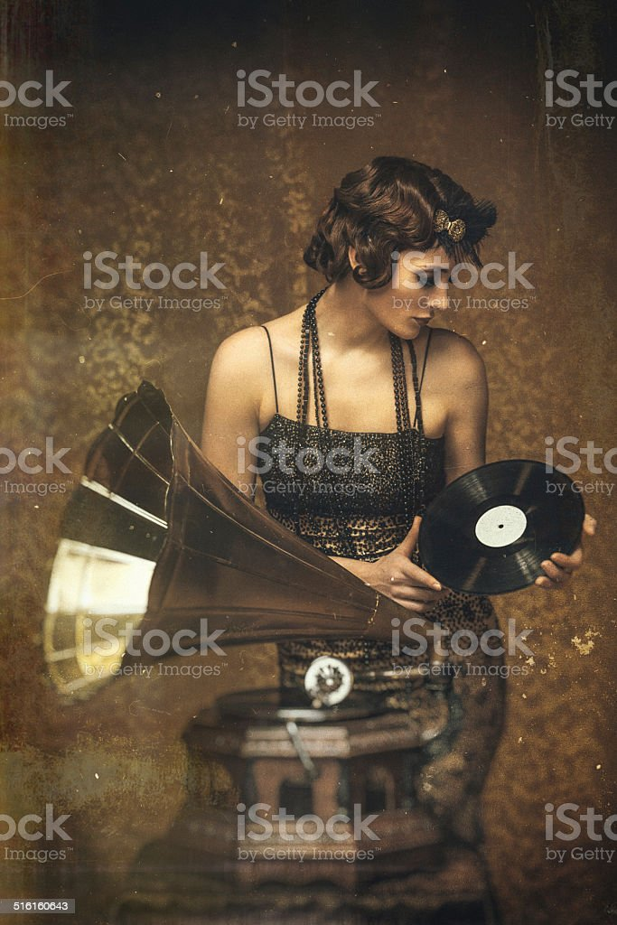 Retro woman playing a vinyl on gramophone -scratched vintage image. stock photo