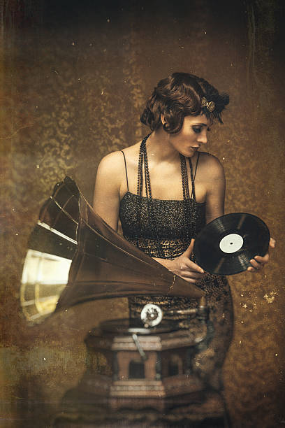 retro woman playing a vinyl on gramophone -scratched vintage image. - 1920s style stock photos and pictures