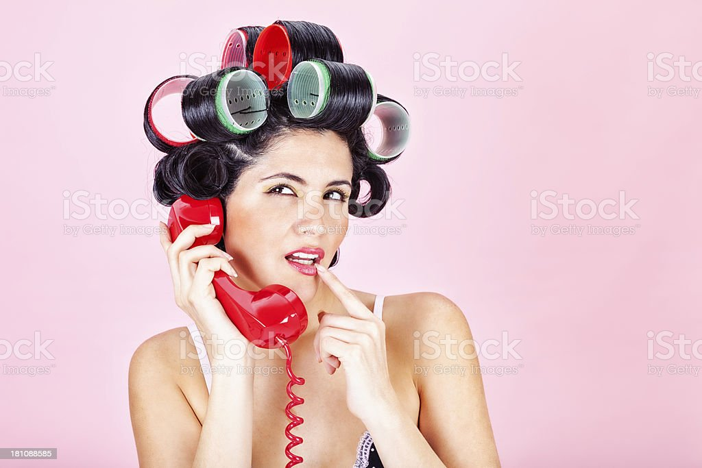 Retro Woman Talking on Red Telephone stock photo