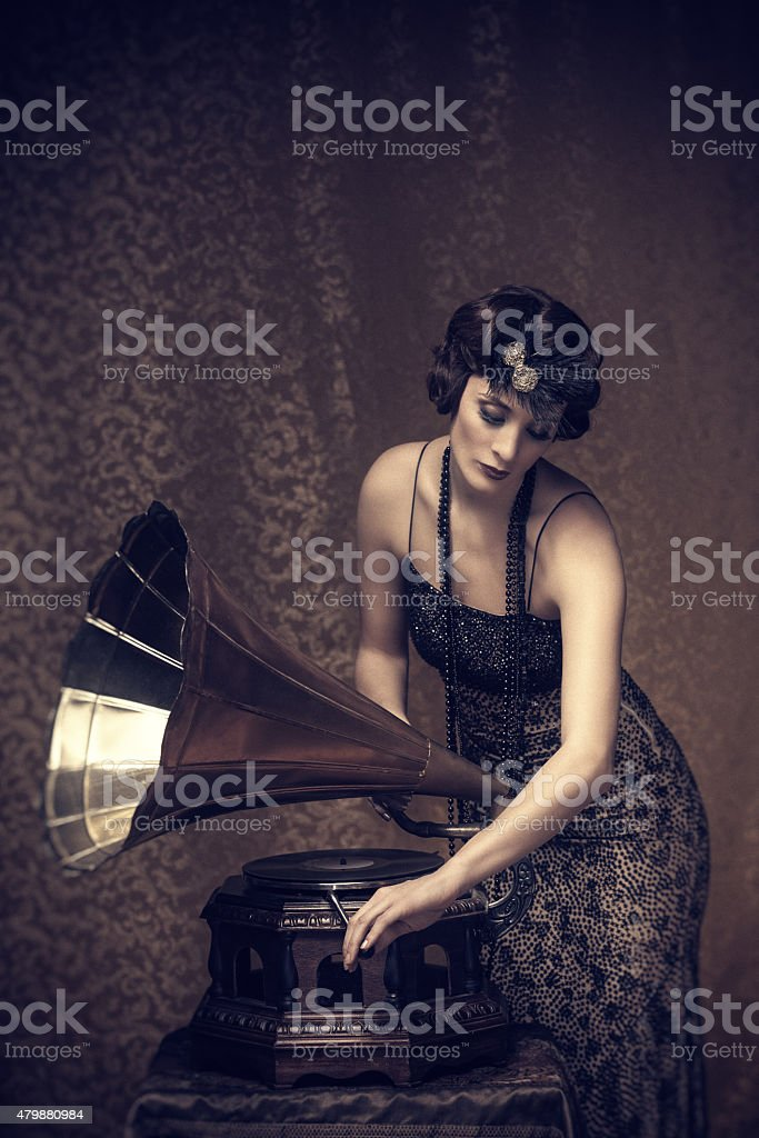 Retro woman winding up a gramophone stock photo