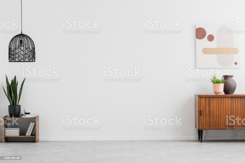 Retro, wooden cabinet and a painting in an empty living room interior with white walls and copy space place for a sofa. Real photo. stock photo