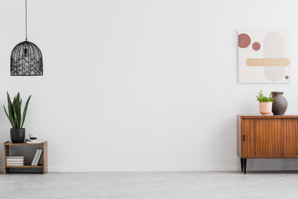 retro, wooden cabinet and a painting in an empty living room interior with white walls and copy space place for a sofa. real photo. - stile minimalista foto e immagini stock