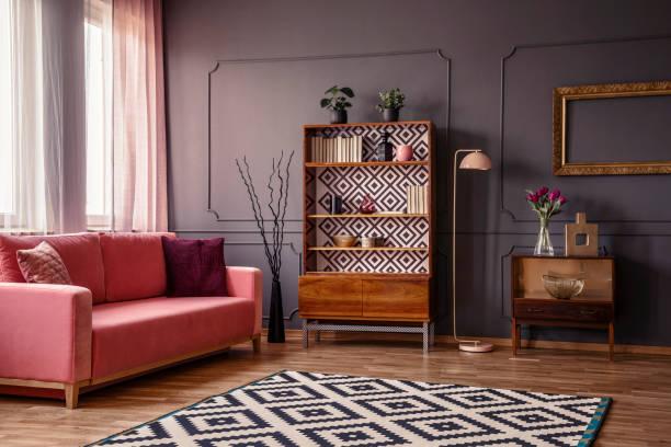 retro-holzschrank mit büchern und dekor stehen im dunklen raum innenraum mit rosa sofa, teppich und blumen in glasvase - teppich geometrisch stock-fotos und bilder