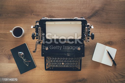 Vintage writing desk with retro typewriter. Top view thirties. Author, writing, journalism concept