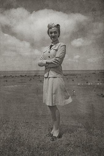 Retro WW2 Navy WAVES  female soldier. Uniform is seersucker summer dress work uniform. Rank is Yeoman 1st Class. Beach background scene includes anti tank obstacles.