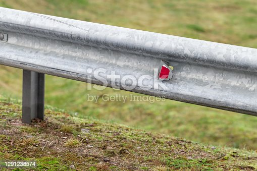 Retroreflector, warning optical unit is on a metal guardrail. Highway safety equipment, close-up