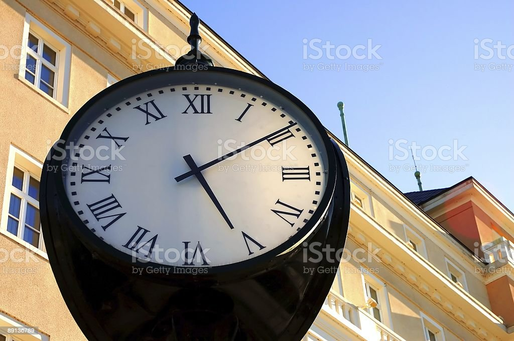 retro-style clock with a building in the background stock photo