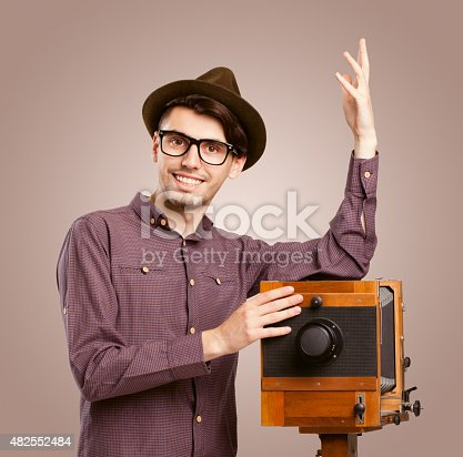 istock Retro-styled photographer with antique wooden camera 482552484