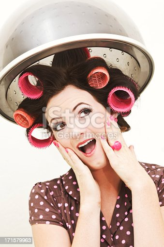 Retrostyled Young Woman In Curlers Under Salon Hairdryer