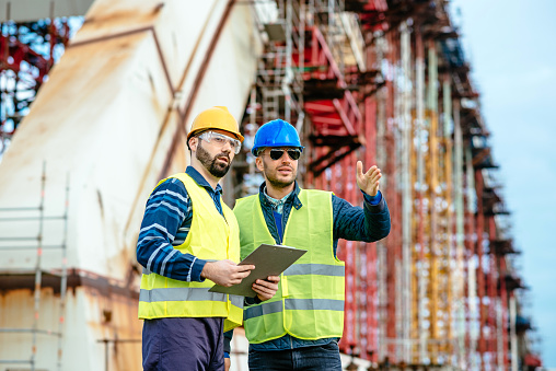 Two experts engineers in protective helmets and fluorescent vests showing the construction site and building activities after the successful project phase. Image taken with Nikon D800 and 85mm developed from RAW in XXXL size, in Novi Sad, Serbia, Central Europe, Europe