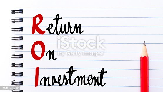 ROI Return On Investment written on notebook page with red pencil on the right