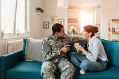 Happy African American Male Soldier In Military Uniform and His Wife Enjoying One Another While Drinking Coffee at Home. Homecoming, Reunion, Returning Home to Family and Happiness Concept