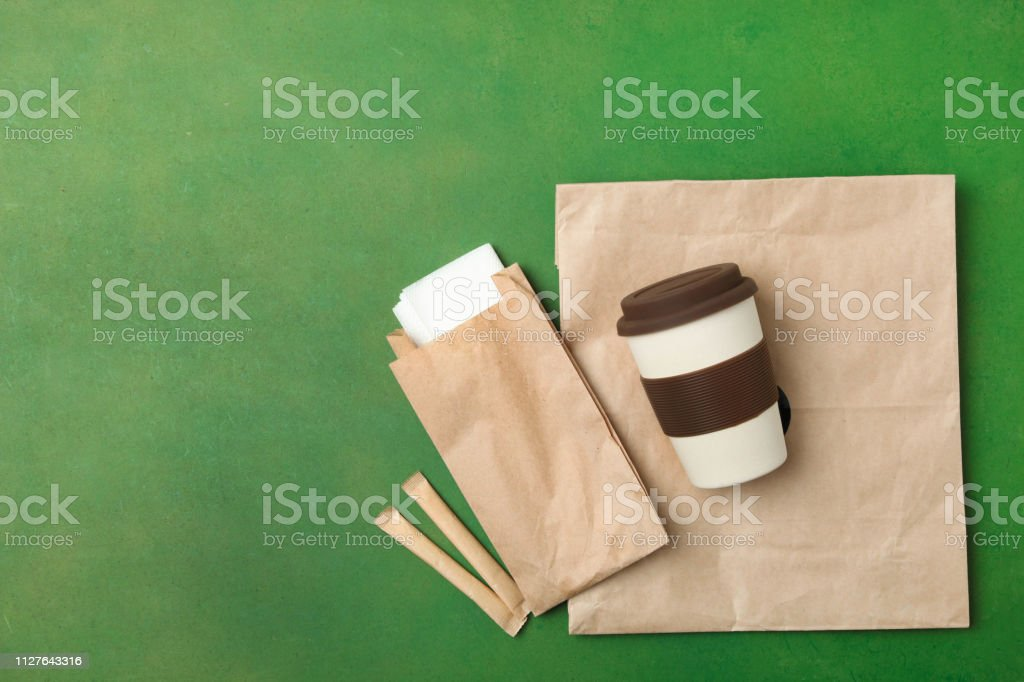 Reusable bamboo glass and craft packages on a green background. Flat...