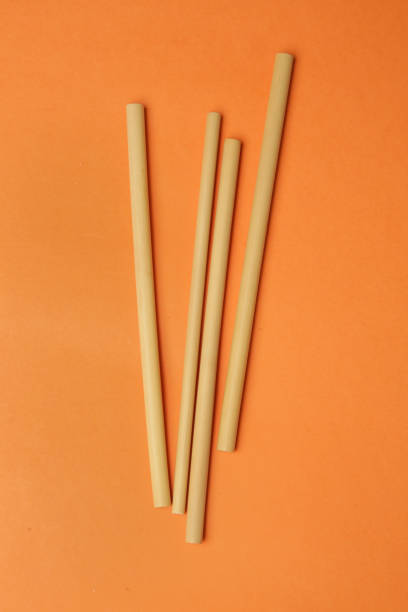 Reusable bamboo straws on the orange background, say no to plastic straws concept Reusable bamboo straws on the orange background, say no to plastic straws concept drinking straw stock pictures, royalty-free photos & images