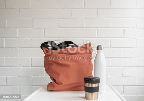 Reusable coffee cup, insulated drink bottle and shopping tote bag on white table against brick wall with copy space