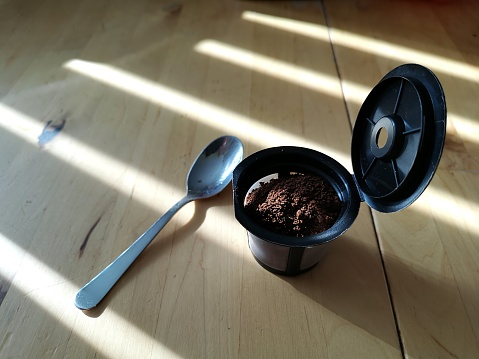 Close-up of a reusable coffee pod, freshly filled with ground coffee, on a kitchen table.