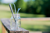 Reusable glass jar sitting on a wooden deck filled with stainless steel straws on a warm summer day outdoors.
