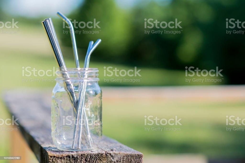 Reusable glass jar full of stainless steel straws stock photo