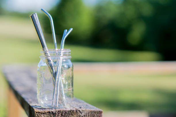 Reusable glass jar full of stainless steel straws Reusable glass jar sitting on a wooden deck filled with stainless steel straws on a warm summer day outdoors. drinking straw stock pictures, royalty-free photos & images