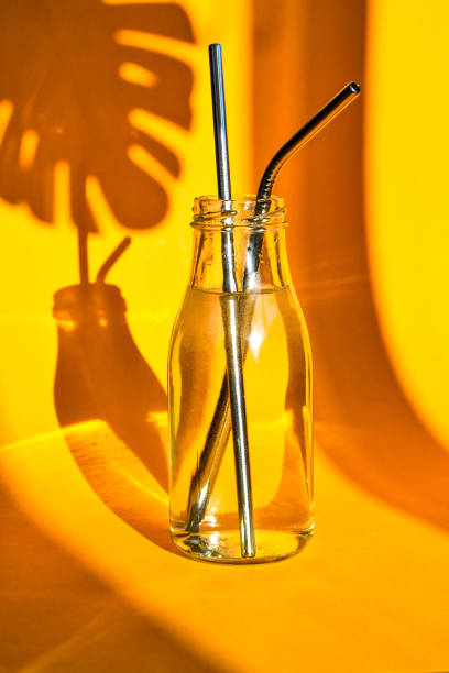 Reusable Metal Straws in glass bottle with water on yellow background with plant shadow - Stainless Steel, Eco-Friendly Drinking Straw Set. Zero waste. Plastic free stock photo