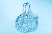 istock Reusable net bag or mesh shopper on blue paper background. Zero waste, plastic free concept. Top view. Eco friendly mesh shopper. Banner with copy space 1154314084