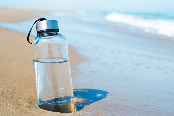 reusable water bottle on the beach stock photo